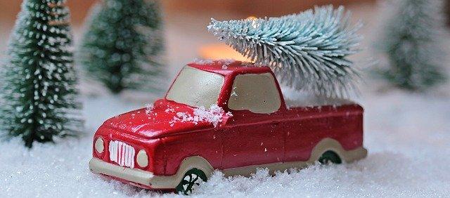 Miniatúra červeného auta v snehu so stromčekom na streche.jpg