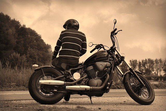 muž sediaci na motorke