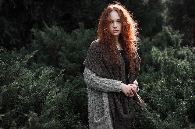 Žena s dlhými vlasmi stojí v prírode