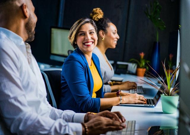 Usmiati ľudia v kancelárii pri počítačoch