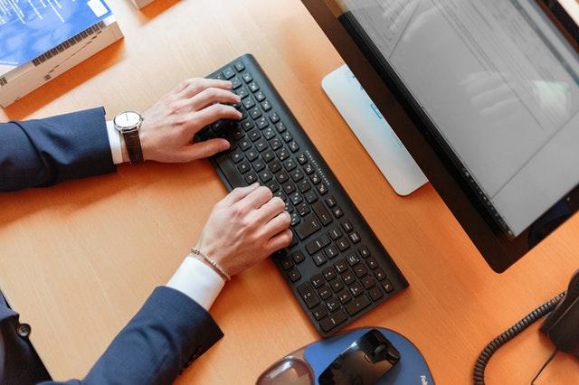Muž v modrom obleku v kancelárii pri stole